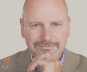 Image shows Martin Crump a man in his 50's with a grey goatee. Martin is wearing a suit with blue and white stripey shirt